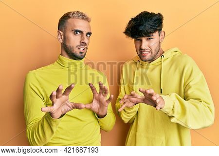 Homosexual gay couple standing together wearing yellow clothes disgusted expression, displeased and fearful doing disgust face because aversion reaction. with hands raised