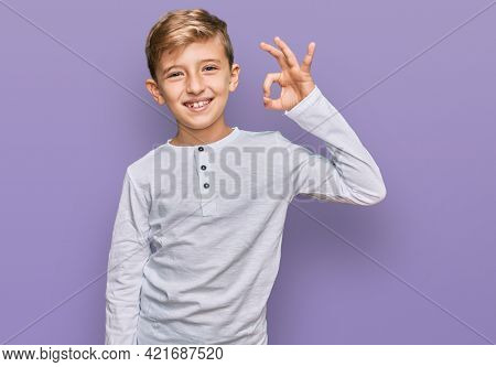 Little caucasian boy kid wearing casual clothes smiling positive doing ok sign with hand and fingers. successful expression.