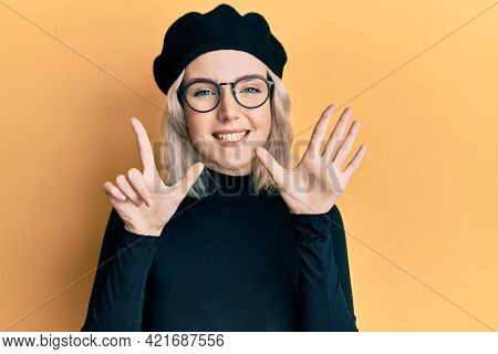 Young blonde girl wearing french look with beret showing and pointing up with fingers number seven while smiling confident and happy.