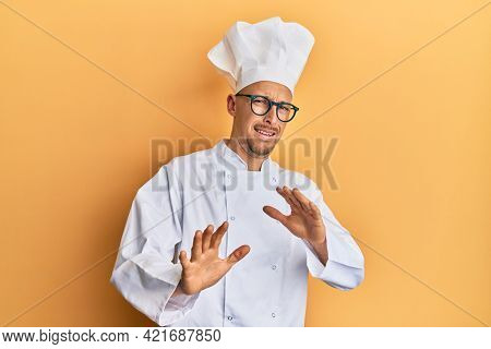 Bald man with beard wearing professional cook uniform disgusted expression, displeased and fearful doing disgust face because aversion reaction. with hands raised