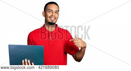 Young african american man working using computer laptop pointing finger to one self smiling happy and proud