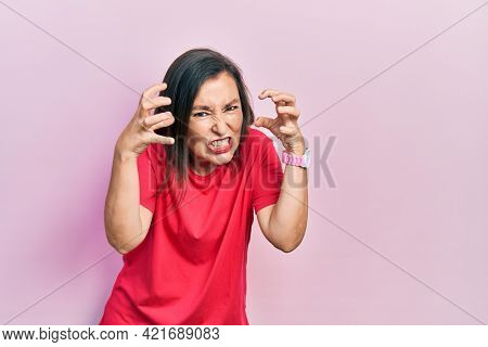 Middle age hispanic woman wearing casual clothes shouting frustrated with rage, hands trying to strangle, yelling mad