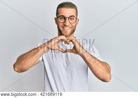 Young caucasian man wearing casual clothes and glasses smiling in love doing heart symbol shape with hands. romantic concept.