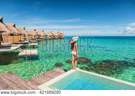 Travel luxury resort woman overwater bungalow hotel. Luxury vacation hotel in Tahiti woman relaxing at infinity pool in French Polynesia travel summer holiday.