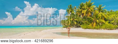 Beach vacation paradise woman tourist walking alone on remote island in the tuamotu islands, French Polynesia. Luxury travel destination. Panoramic banner.