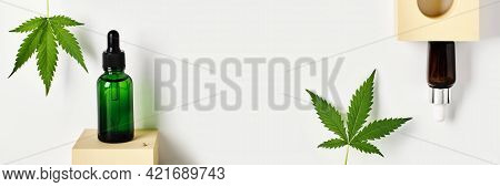 Banner With Glass Bottles With Cbd Oil And Cannabis Leaves On Abstract Geometric Podiums. Cosmetics