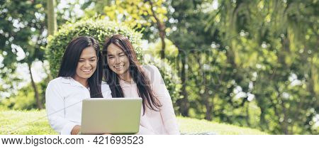 Banner Asian Two Women Talking Using Laptop Sit On Green Meadow At Green Park. Panorama Friendship G