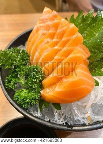 Sliced Fresh Raw Salmon Sashimi Served On Ice In Japanese Restaurant. Fresh Raw Salmon Fish Sashimi