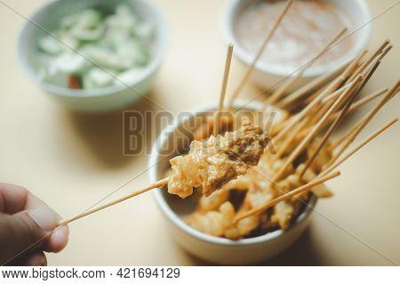 A Hand Having Pork Satay And Dipping Peanut Sauce