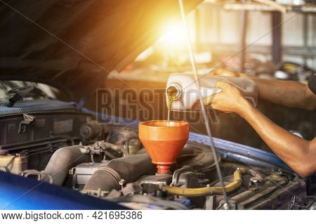 Old Car Oil Change Mechanic. Add New Oil To The Car. Pour Fresh Oil At The Service Station.