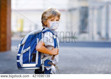 Happy Little Kid Boy With Medical Mask And Backpack Or Satchel. Schoolkid On Way To School. Healthy