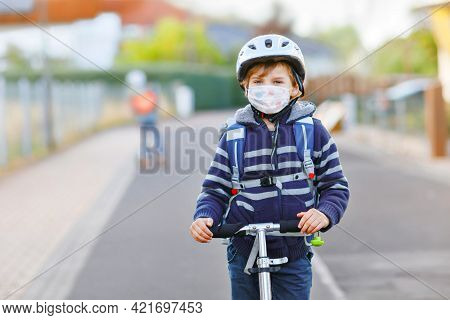 Little Kid Boy With Medical Mask On The Way To School With Scooter. Child With Satchel. Schoolkid. L