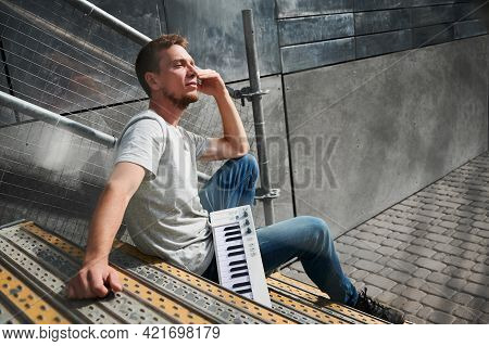 Side View Of Male With Piano Keyboard Is Sitting On Stairs. Young Man In Grey T-shirt Is Resting On