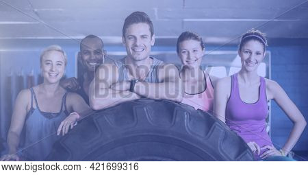 Composition of smiling men and women in fitness class leaning on tyre. sport, fitness and active lifestyle concept digitally generated image.