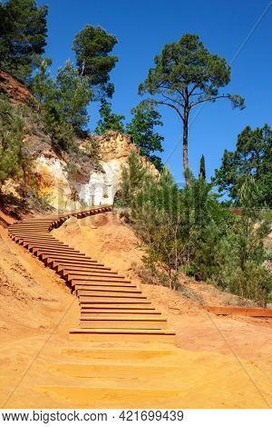 Walk along the most beautiful red-yellow-orange route on the wooden deck for tourists. The rocks are covered with forest. The village of Roussillon. Picturesque rocks from natural ocher.