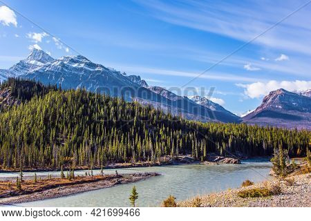 Great Canadian Rockies. The sharp peaks of the Rocky Mountains are clearly visible against the blue sky. The first snow has already fallen on the peaks. Stunning Abraham Lake