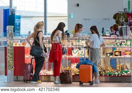 Tourist Girls With Suitcases At The Airport Buy Souvenirs At A Kiosk. Chelyabinsk, Russia, May 17, 2