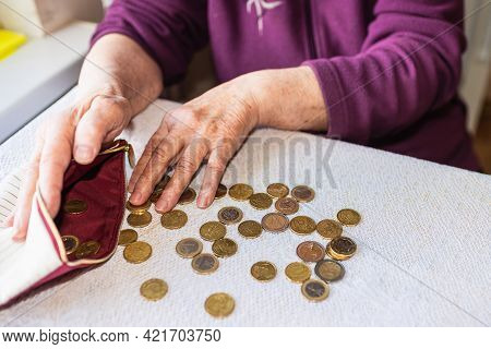 Concerned Elderly Woman Sitting At Home And Counting Remaining Coins.old Woman Sitting Miserably At