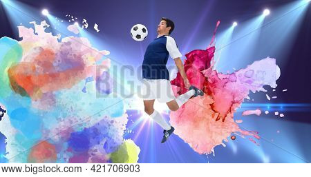 Composition of football player with ball over colourful splodges and sports stadium background. sports event and competition concept digitally generated image.