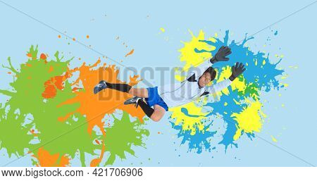 Composition of football goalkeeper over colourful splodges on blue background. sports event and competition concept digitally generated image.