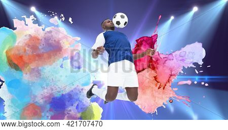 Composition of football player with ball over colourful splodges and sports stadium. sports event and competition concept digitally generated image.