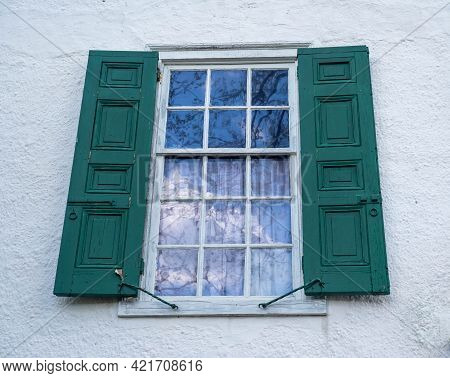 Antique Window In A White House With A Beautiful Reflection Of The Blue Sky And White Clouds. Gorgeo