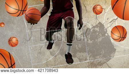 Composition of basketball player and basketballs over basketball court. sport event and competition concept digitally generated image.