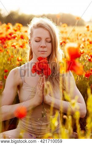 Portrait Of A Beautiful Girl With A Bouquet Of Poppies In Her Hands Meditating On A Poppy Field. Yog