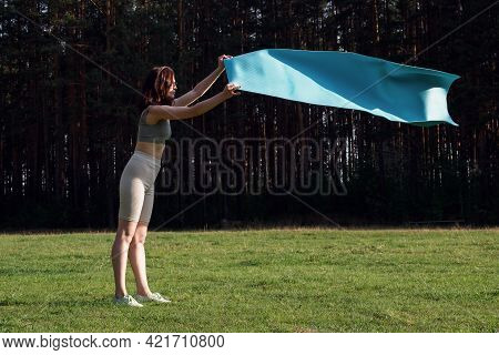 A Young Woman In A Sports Uniform Unwraps A Yoga Mat In The Woods. Start Of Outdoor Training In The