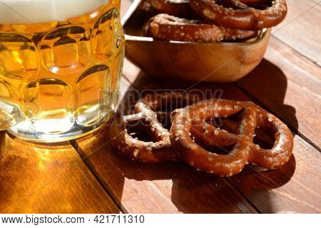 Hard Pretzels Or Salted Pretzels Snack For Party On Rustic Wooden Table With Glass Of Beer