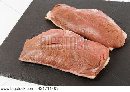 Two raw duck breast fillets on black slate plate, close-up