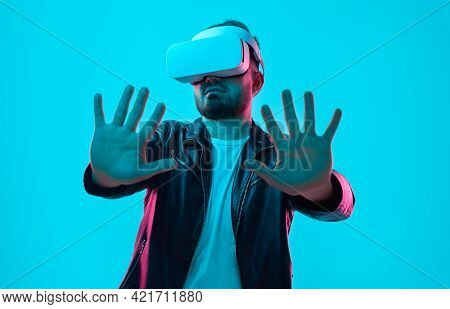 Male In Vr Headset Interacting With Virtual Reality With Outstretched Arms In Studio With Neon Light
