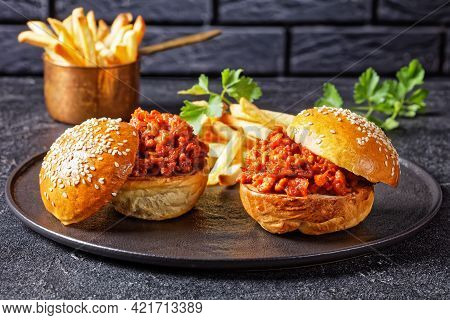 Sloppy Joe Sandwiches With French Fries On A Black Plate With A Brick Wall At The Background, Close-