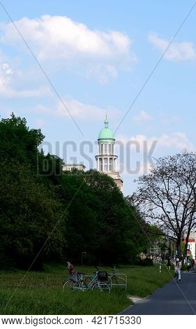Berlin, Germany, 25 April 2021, Domed Tower At Frankfuter Tor With Old Trees At The End Of Karl-marx