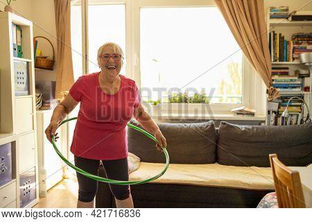 Older woman hula hooping at home