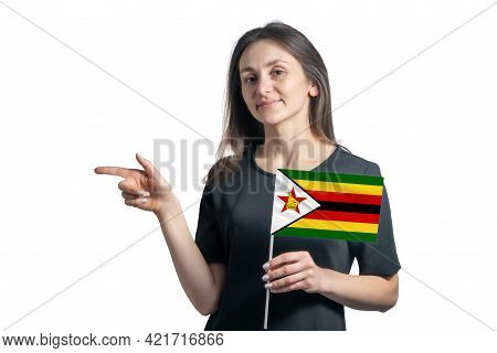 Happy Young White Woman Holding Flag Zimbabwe And Points To The Left Isolated On A White Background.