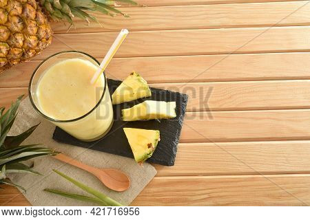 Two Glasses With Pineapple Juice With Milk And Pineapple Portions On Wooden Table With Pineapples Ar