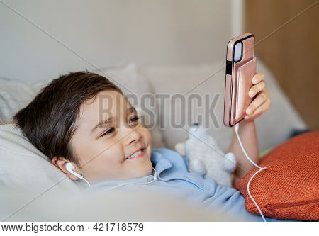 Close Up Smiling Face Of Cute Boy Listening To Music Via Mobile Phone, Kid Holding Cell Phone. Candi