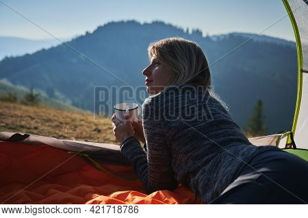 Close Up Back View Of Pretty Girl Who Relaxing In Her Tent During Hiking In The Mountains, Holding M