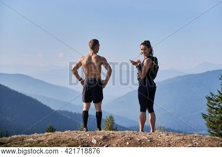 Back View Couple Of Hikers Standing On Rocky Top Of One Of Mountain Hills. Man Putting Hands Waist A