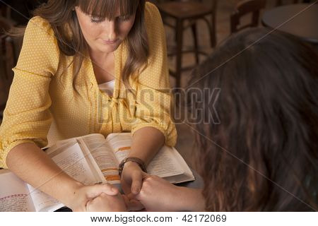 Two women hold hands and pray as they study the bible. poster