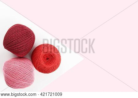 Crimson, Red And Pink Cotton Thread Balls And Crochet Hook On Geometric Pink And White Background.th
