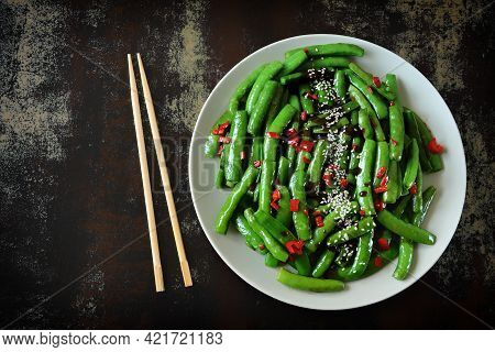 Green Pea Pods On A Plate With Sesame Seeds And Soy Sauce. Chinese Style Pods.