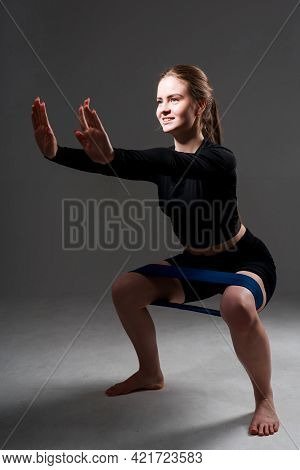 Girl Trainer Doing Squats Using An Elastic Band Putting Her Palms Forward On A Dark Background