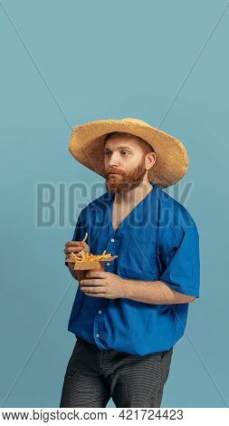 Young Red Headed And Bearded Man In Straw Hat Standing Isolated Over Blue Bacground. Eras Comparison