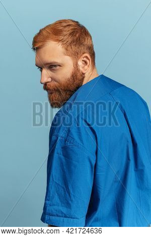 Close-up Portrait Of Young Red Headed And Bearded Man Isolated Over Blue Bacground. Eras Comparison