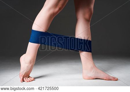 Photo Of Female Legs Stretching An Elastic Band Doing A Workout To Strengthen Leg Muscles