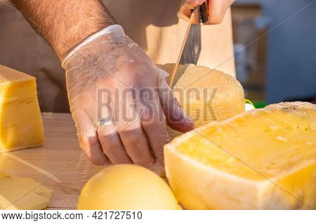 Shopkeeper's Hands Cutting A Head Of Cheese