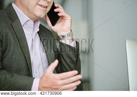 Close-up Of Smiling Caucasian Businessman In Formalwear Gesturing Hand While Discussing Project By P