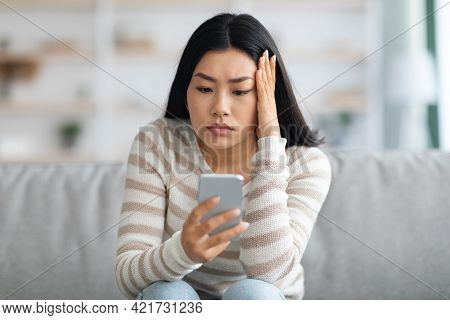 Bad News. Upset Asian Female Holding Smartphone, Looking At Screen With Worry